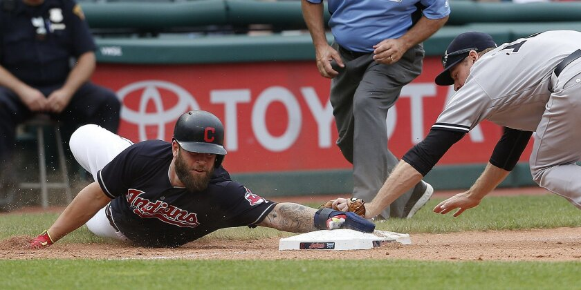 Cleveland Indians' Mike Napoli, left, advances to third on a hit by Jose Ramirez as New York Yankees' Chase Headley, right, covers the base during the seventh inning of a baseball game Saturday, July 9, 2016, in Cleveland. (AP Photo/Ron Schwane)