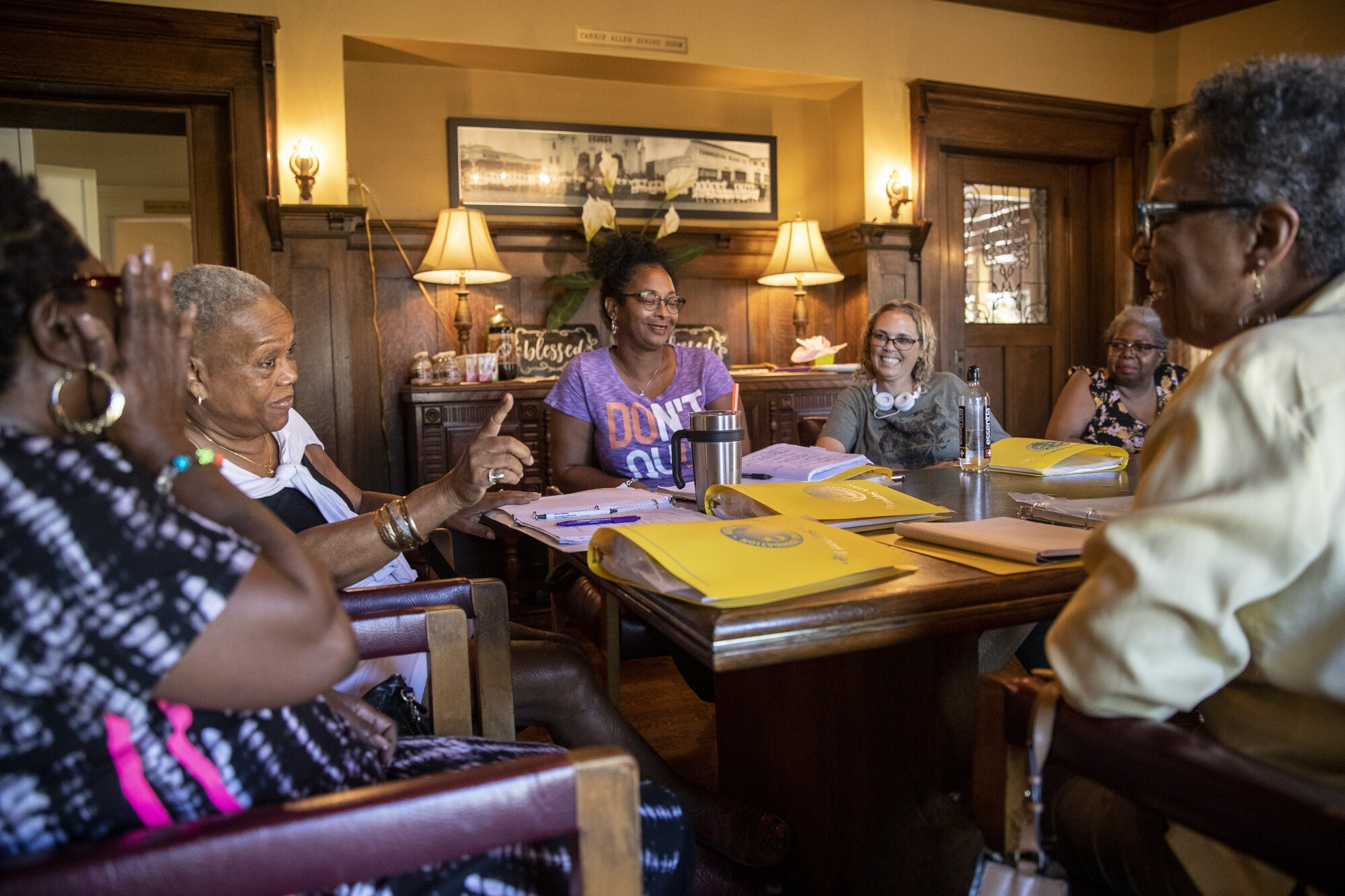 Women at a support group for family caregivers sit and talk around a table.
