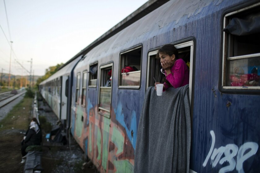 In this Saturday, May 7, 2016 photo, a Syrian girl looks out train window that she lives with her family in the sprawling refugee and migrant tent city of Idomeni, on Greece's northern border with Macedonia. The evacuation of Idomeni has dashed the dreams of thousands migrants and refugees who had