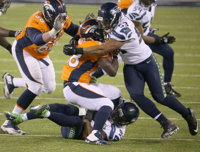 Malcolm Smith of the Seattle Seahawks (53) stops Montee Ball of the Denver Broncos.