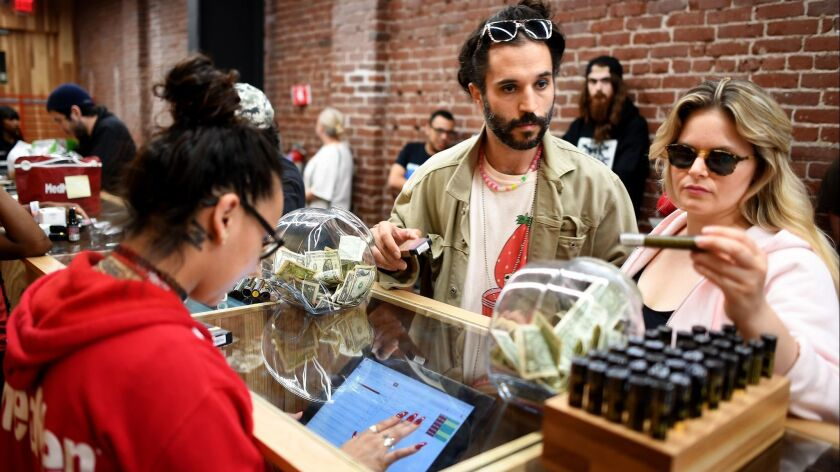 A woman looks at a marijuana strain at MedMen, standing next to a man and across the counter from a woman working on a touchscreen.