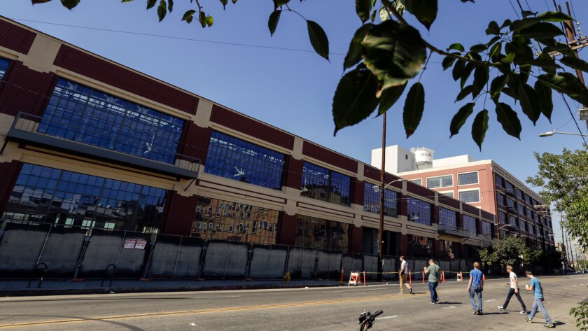 Warner Music Group plans to move hundreds of employees from Burbank and the Westside into a renovated former auto plant in the downtown Arts District.