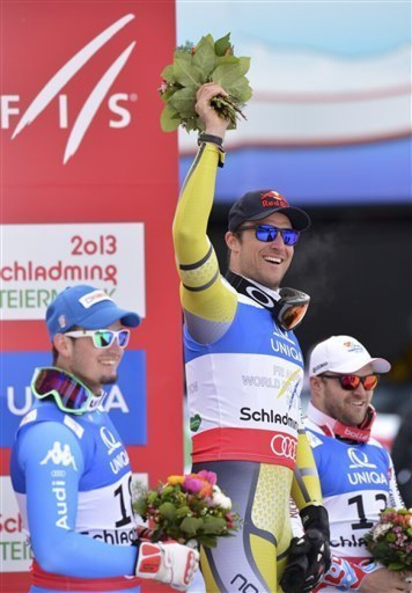 Norway's gold medal winner Aksel LundSvindal is flanked by Italy's silver medal winner DominikParis, left, and France's bronze medalist DavidPoisson during the flower ceremony for the men's downhill at the Alpine skiing world championships in Schladming, Austria, Saturday, Feb. 9, 2013. (AP Photo/Kerstin Joensson)