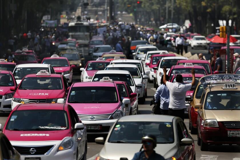 Cientos de taxistas bloquean un bulevar de la Ciudad de México en protesta por Uber y otros servicios que pueden ser solicitados a través de teléfonos celulares. (AP Foto/Marco Ugarte)
