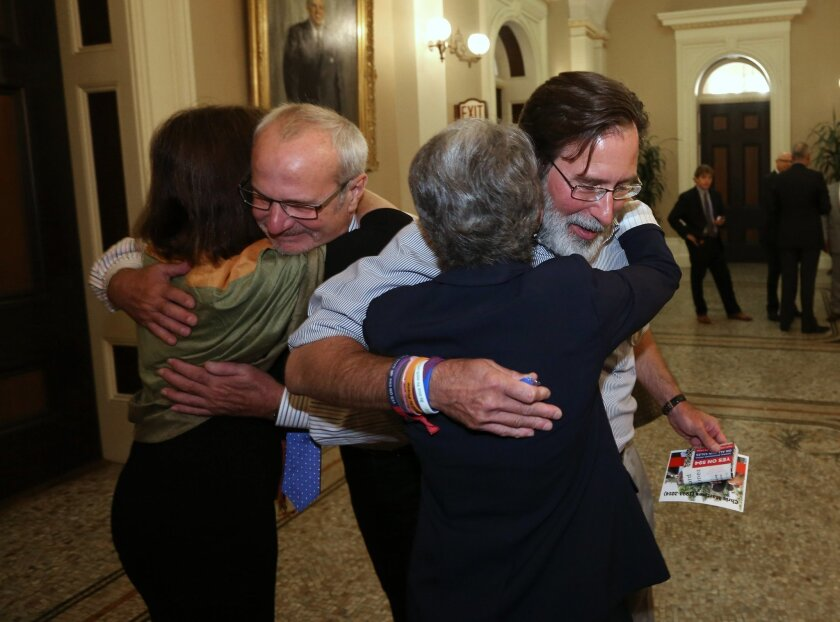 FILE -- In this Aug. 27, 2014 file photo, Richard Martinez, right, whose son, Christopher Ross Michaels-Martinez was killed in a shooting spree in Isle Vista last May, hugs State Sen. Hannah-Beth Jackson, D-Santa Barbara, as Bob Weiss, whose daughter Veronika, whose daughter was also killed in the same shooting spree, hugs, Assemblywoman Nancy Skinner, D-Berkeley, after the bill they carried, that allows family members to ask a judge to remove firearms from a relative who appears to pose a threat was approved by the Senate in Sacramento, Calif. Gov Jerry Brown signed the measure, AB1014, Tuesday, Sept. 30, 2014, that will allow law enforcement and immediate family members to seek are restraining order removing fire arms for 21 days. (AP Photo/Rich Pedroncelli,file)