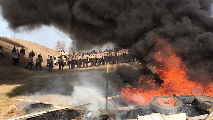 Tires burn as armed soldiers and law enforcement officers stand in formation to force protesters off disputed land.