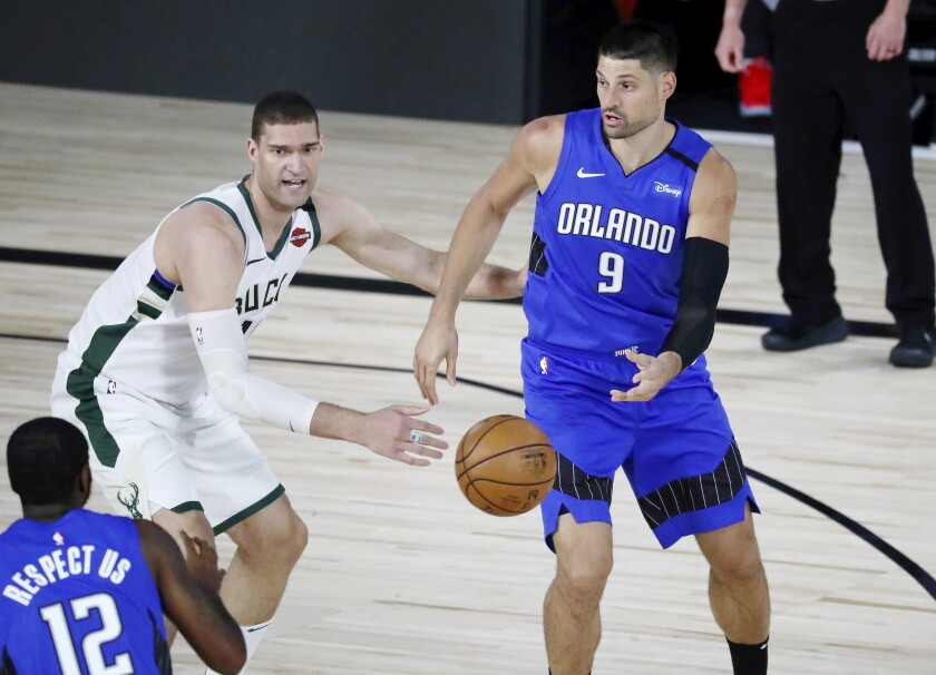 Magic center Nikola Vucevic passes the ball to forward Gary Clark while defended by Bucks center Brook Lopez during Game 1.