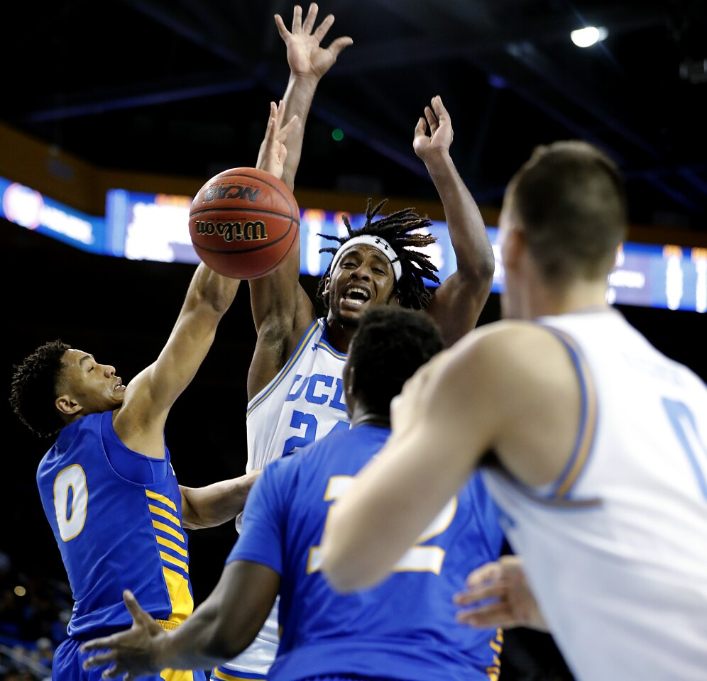 LOS ANGELES, CALIF. - NOV. 21, 2019. Bruins forward Jalen Hill dishes a pass off to teammate Alex Olesinski in the second half at Pauley Pavilion in Westwood on Thursday night, Nov. 21, 2019. (Luis Sinco/Los Angeles Times)