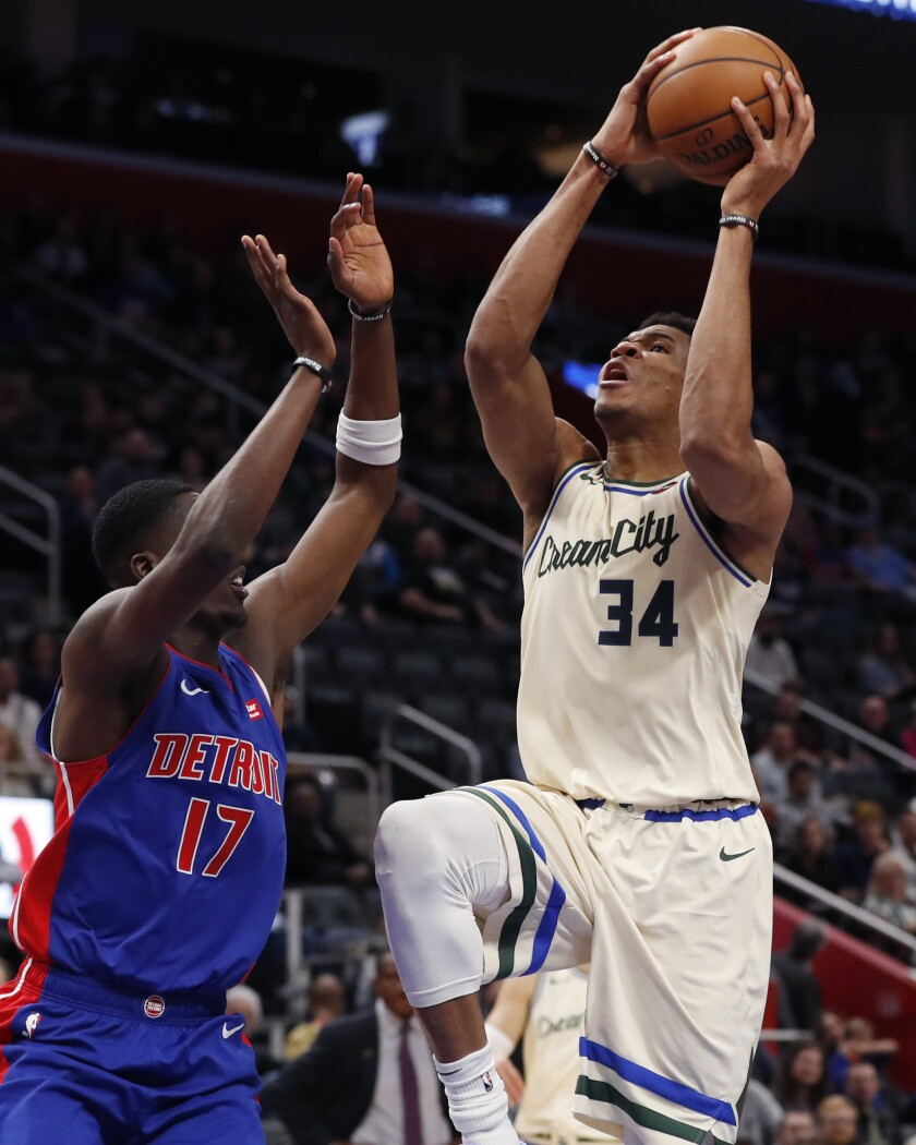 Milwaukee Bucks forward Giannis Antetokounmpo (34) attempts a layup as Detroit Pistons guard Tony Snell (17) defends during the first half of an NBA basketball game, Wednesday, Dec. 4, 2019, in Detroit. (AP Photo/Carlos Osorio)
