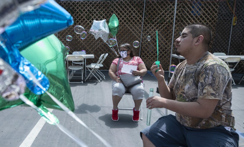 A man sits in a chair blowing bubbles outside. Green, silver and blue balloons are also in view. A woman is also seated.