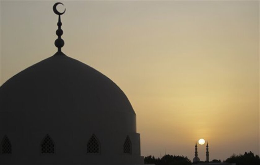 In this file photo, the sun sets behind minarets of a mosque a few minutes before Iftar, the meal served at dusk when Muslims break their day-long fast during the month of Ramadan. Below, the author looks for a silver lining during the coronavirus pandemic.