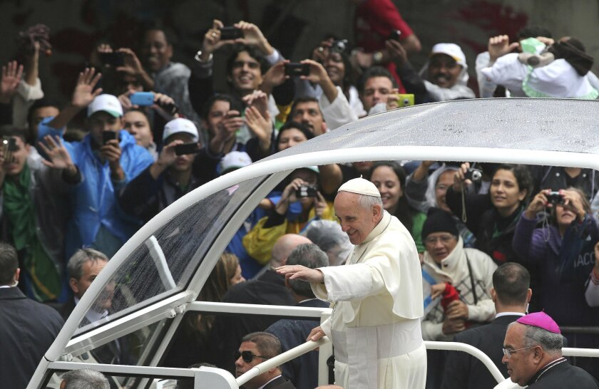 FILE - In this July 27, 2013 file photo, Pope Francis waves to people from his popemobile in Rio de Janeiro, Brazil. Latin Americans who were born into Roman Catholic families have increasingly left the faith for Protestant churches, while many others have dropped organized religion altogether in a