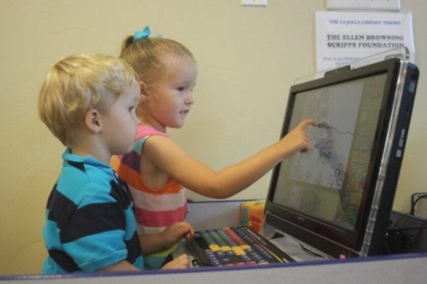 Robbie and katie Degnaus use the touch screen to color a picture.