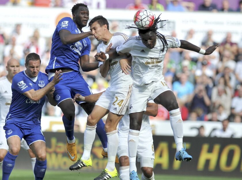 Swansea City's Bafetimbi Gomis, right, goes for a header during the English Premier League soccer match against Everton at the Liberty Stadium, Swansea, Wales Saturday Sept. 19, 2015. (Simon Galloway/PA via AP) UNITED KINGDOM OUT PHOTOGRAPH