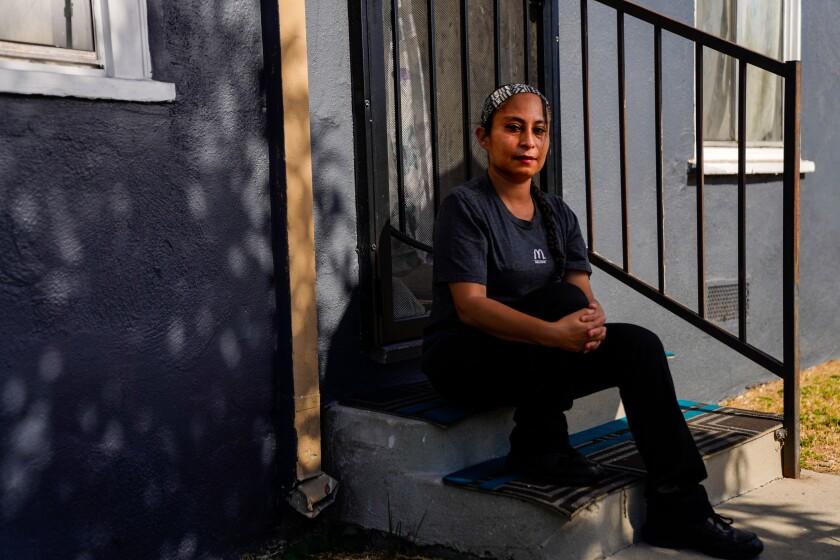 A woman sits on porch steps below a screen door at a dark gray building