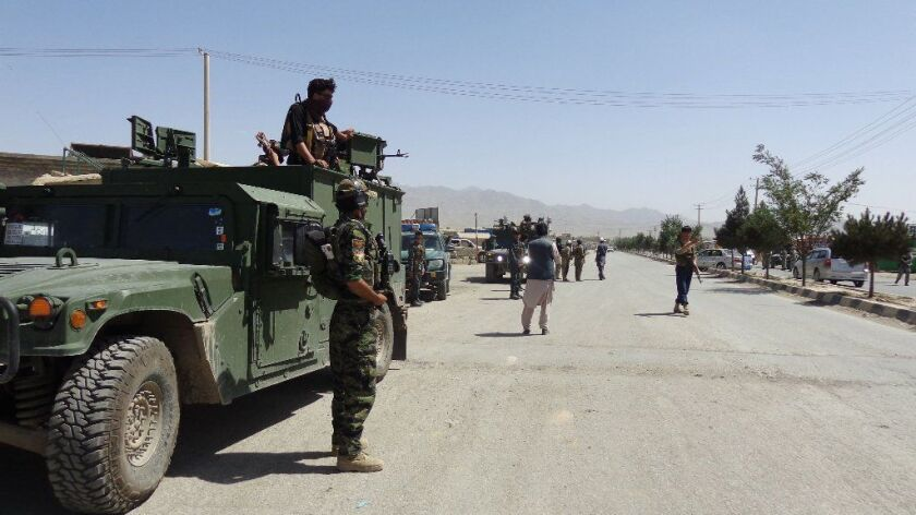 Security forces monitor a road near a mosque attacked by suicide bombers in Paktia, Afghanistan, on Friday.