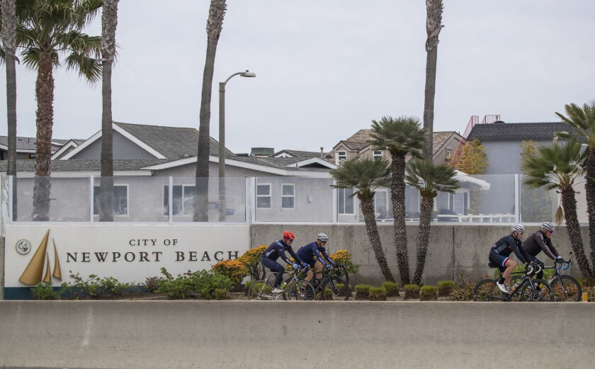People ride bikes past a sign welcoming them to Newport Beach on March 31.
