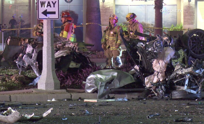 First responders look over the scene of a crash Tuesday morning in Newport Beach that killed one person and injured another.
