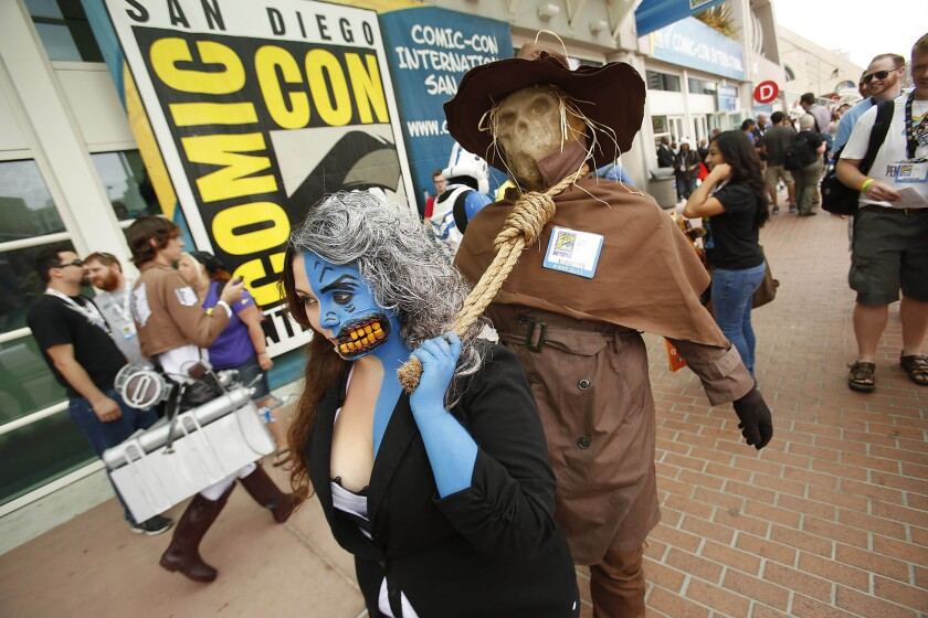 As Batman character Two-Face, Angie Rodriguez leads Jonathon Antone, cosplaying as Scarecrow, by the neck in front of the San Diego Convention Center at Comic-Con.