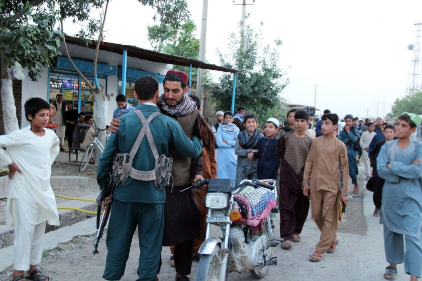 A Taliban militant greets an Afghan police officer during a visit by a group of militants to a bazaar to greet civilians as a goodwill gesture amid a three-day cease-fire on first day of Eid al-Fitr, in Kunduz, Afghanistan, on June 15, 2018.