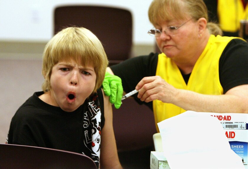 Dakota Reandeau, 11, receives an H1N1 vaccination in January of 2010 at the Escondido Community Center.