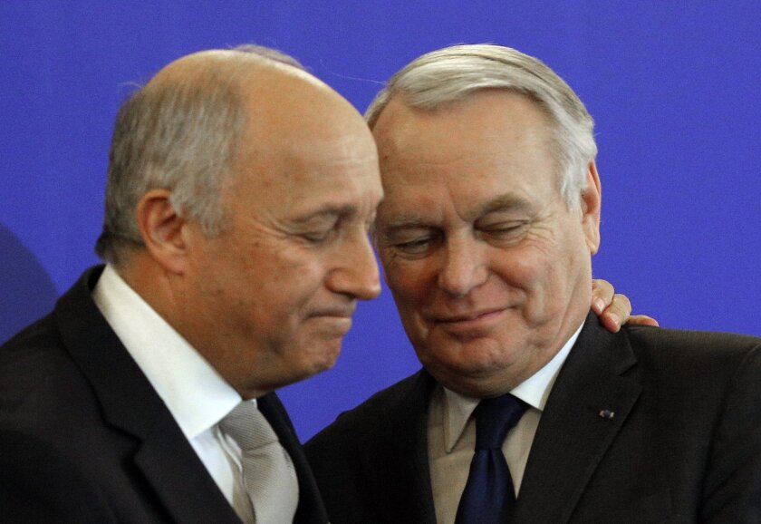 France's new foreign minister Jean-Marc Ayrault, right, shakes hands with outgoing minister Laurent Fabius during the handover ceremony in Paris Friday, Feb. 12, 2016. French President Francois Hollande has named former Prime Minister Jean-Marc Ayrault as the new foreign minister in a government re