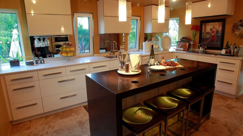 The remodeled kitchen of Lena Brion's home includes a custom island in black Caesarstone, travertine floor tile and several other improvements.