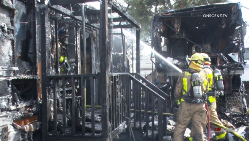 Firefighters extinguish hot spots Friday afternoon after flames tore through two mobile homes in El Cajon.