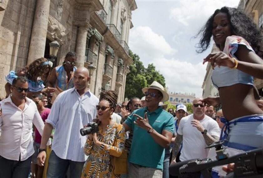 FILE - In this April 4, 2013 file photo, U.S. singer Beyonce and her husband, rapper Jay-Z, are surrounded by bodyguards as they tour Old Havana, Cuba. U.S. Treasury officials on Tuesday, April 9, 2013 said the trip by Beyonce and Jay-Z to Cuba was licensed as an educational exchange. (AP Photo/Ram