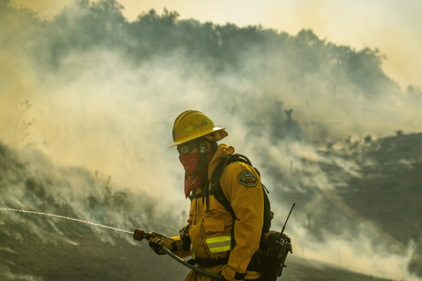 An Orange County Fire Authority firefighter uses a resident's garden hose.