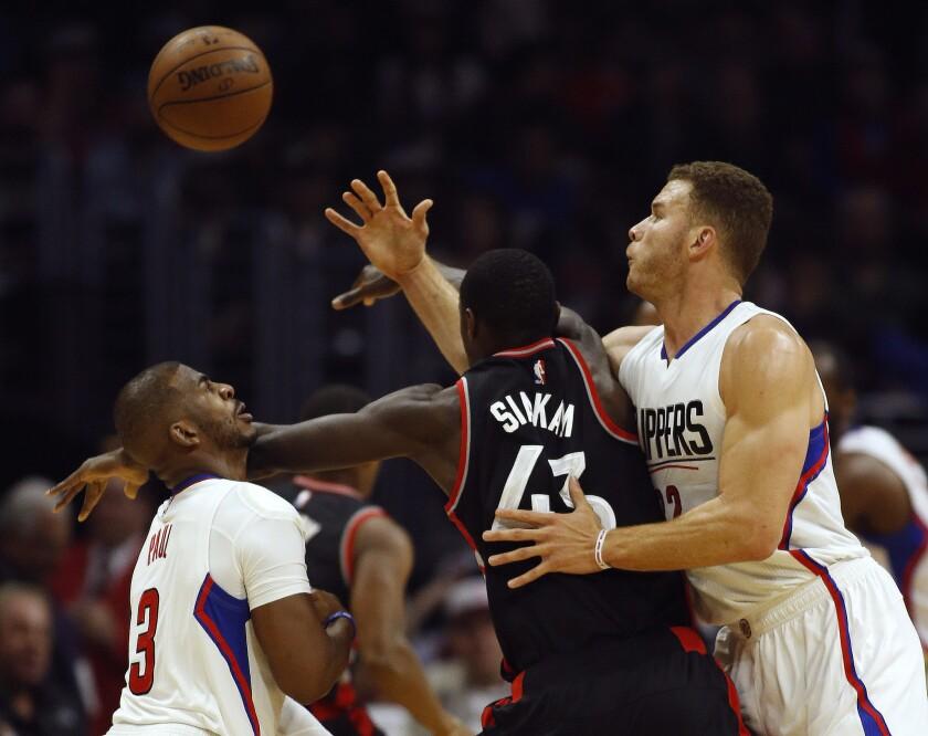 Los jugadores de los Clippers de Los Angeles Chris Paul (izquierda) y Blake Griffin (derecha) pelean un balón con su rival de los Raptors de Toronto Pascal Siakam (centro), en la primera mitad del juego de la NBA que enfrentó a ambos equipos en Los Angeles, el 21 de noviembre de 2016. (AP Foto/Alex Gallardo)