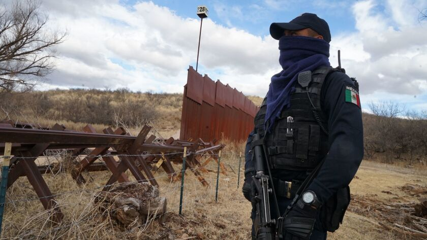 Where the 15-foot steel border fence ends, a barrier made of old locomotive rails and barbed wire begins between Arizona and Mexico. Police from Nogales, Mexico, often respond to incidents along this stretch of the border.