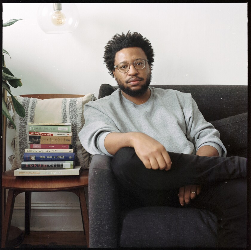 Vinson Cunningham sits on a couch next to a stack of books.