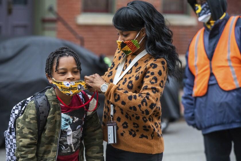 En imagen de archivo del lunes 29 de marzo de 2021, Jenea Edwards, de North Side, ayuda a su hijo Elijah,
