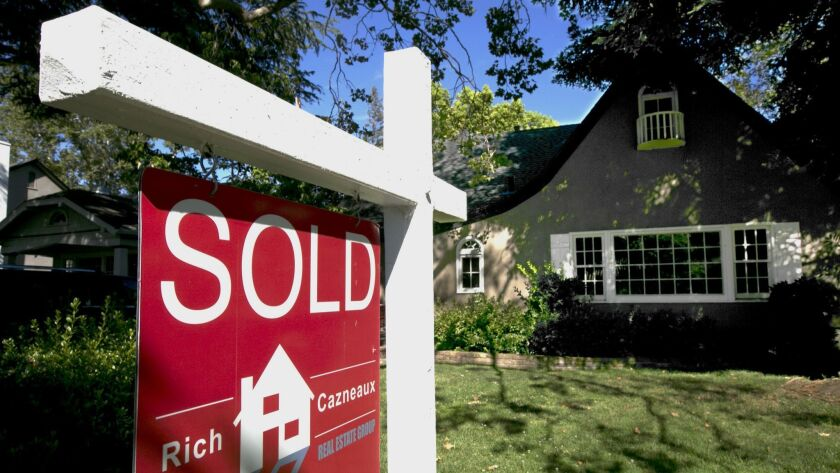 FILE - In this Wednesday, July 5, 2017, file photo, a sold sign is displayed in front of a house in