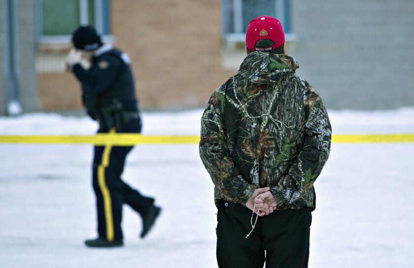 A man holds a rosary as police investigate the scene of a shooting at the community school in La Loche, Saskatchewan, on Saturday, Jan. 23, 2016. The shooting took place on Friday. Saturday, Jan. 23, 2016. (Jason Franson/The Canadian Press via AP)
