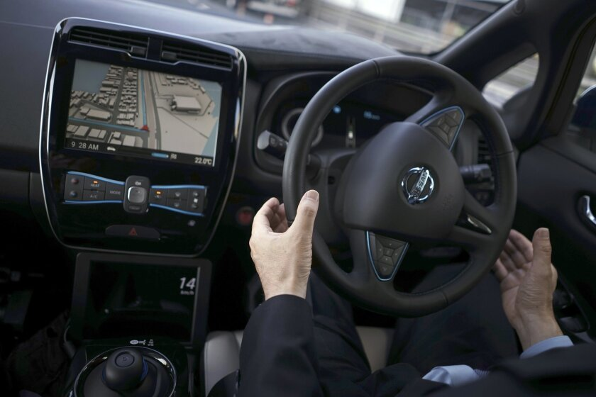 """Nissan Motor Co. General Manager Tetsuya Iijima gets his hands off of the steering wheel of a self-driving prototype vehicle during a test drive in Tokyo, Tuesday, Nov. 3, 2015. Nissan's """"intelligent driving"""" feature is smart enough to navigate intersections without lane markers. It also brakes saf"""