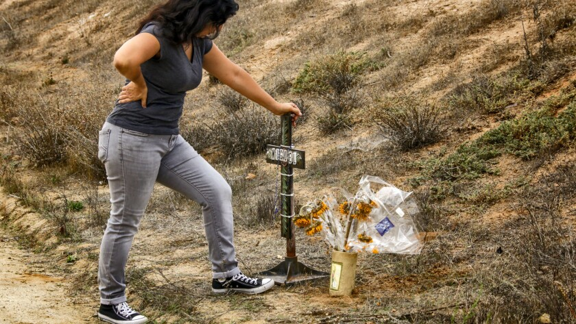 Michelle Glenn offers prayers at a makeshift memorial in front of the home where her cousin, Miguel Ferreyra, and four other adults died in a suspicious fire that gutted a care facility in Temecula.