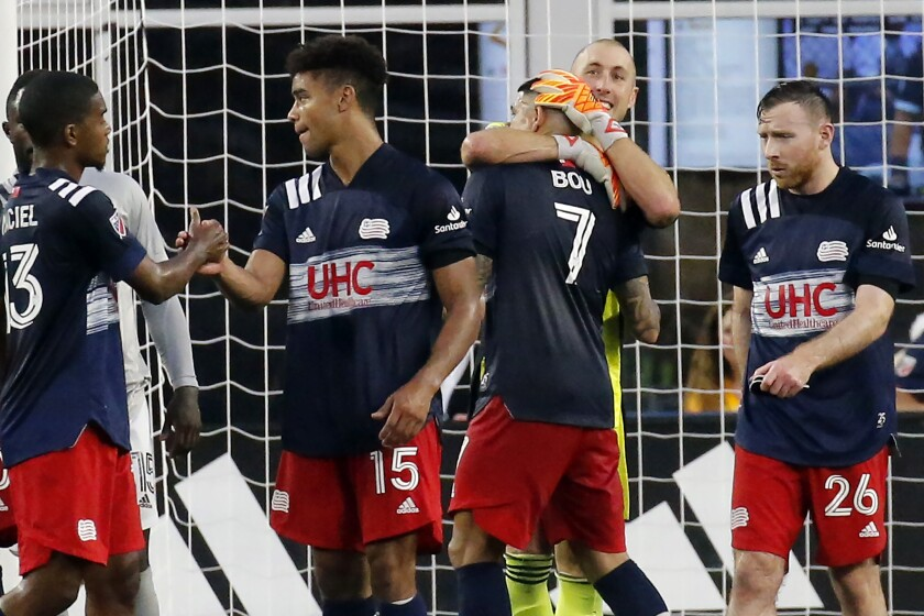 New England Revolution goalkeeper Brad Knighton hugs forward Gustavo Bou (7) following their victory over CF Montreal in an MLS soccer match, Sunday, July 25, 2021, in Foxborough, Mass. (AP Photo/Mary Schwalm)