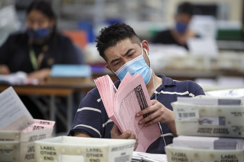 A man in a mask holds and looks closely through a stack of ballots.