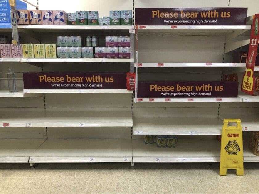 """Empty shelves and signs on the soft drinks aisle of a Sainsbury's store in Rowley Regis in the West Midlands, England, Thursday July 22, 2021. Retailers in England warned Thursday of barren supermarket shelves as more and more staff get """"pinged"""" on their phones to self-isolate because of contact with coronavirus cases. Grappling with staff shortages amid the so-called """"pingdemic,"""" many businesses, such as supermarket chain Iceland, have had to close some stores. (Matthew Cooper/PA via AP)"""