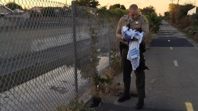 A Los Angeles County sheriff's deputy cradles a baby girl near the Compton site where she was found in a crevice covered with pieces of asphalt.