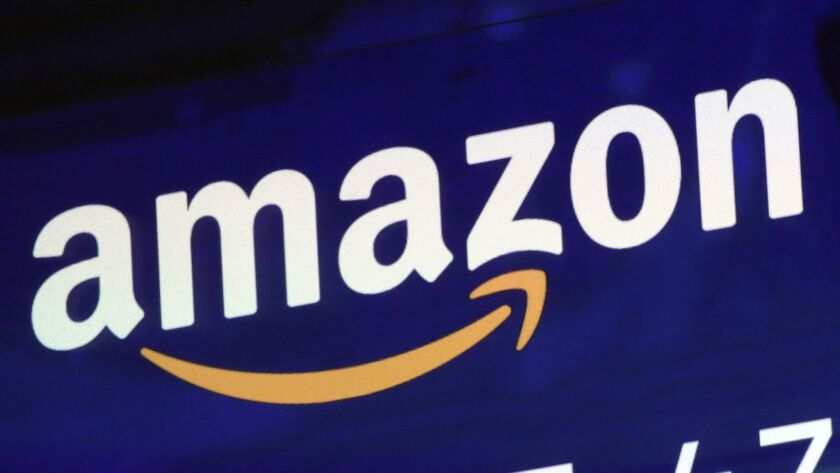 FILE - In this Friday, July 27, 2018 file photo, the logo for Amazon is displayed on a screen at the