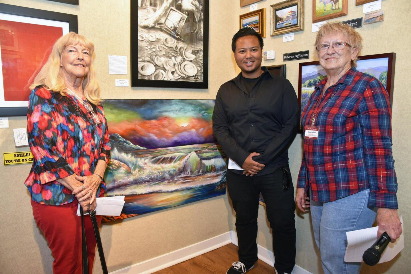 """MiraCosta Campus Art Gallery Director Diane Adams, Mira Costa art student scholarship recipient Jermaine Morales, in front of his """"Off the Coast of Somewhere Beautiful"""" painting, Mother's Day Tour Chair/artist Sharon Hoffman"""