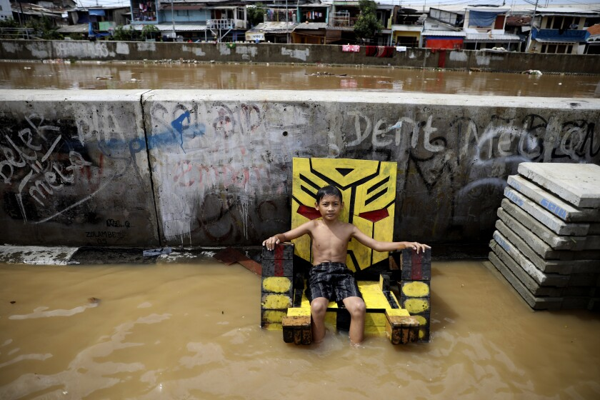 A young boy sits on a chair in a flooded neighborhood in Jakarta, Indonesia, on Thursday.