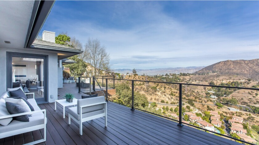 The clean, contemporary home expands to a spacious deck that takes in sweeping views of Griffith Park and the Hollywood sign.