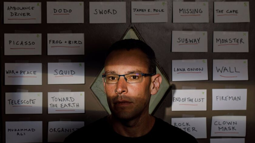 Ben Loory stands before story titles pinned to his door.