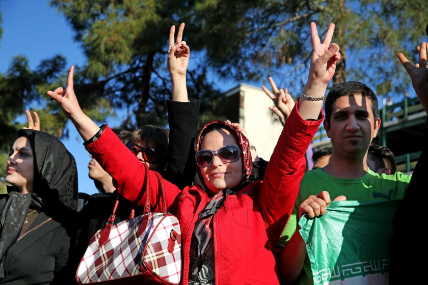 Iranians flash the victory sign while waiting for arrival of Foreign Minister Mohammad Javad Zarif from Lausanne, Switzerland, at the Mehrabad airport in Tehran on April 3.