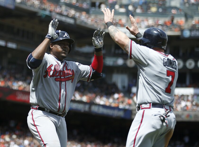 Atlanta Braves' Juan Uribe, left, is congratulated by teammate Jonny Gomes (7) after hitting a two-run home run against the San Francisco Giants during the seventh inning of a baseball game, Sunday, May 31, 2015, in San Francisco. (AP Photo/Tony Avelar)