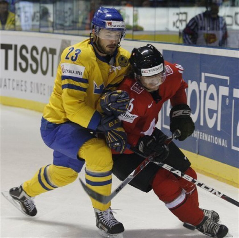 Sweden's Niklas Persson, left, fights for a puck with Raphael Diaz right, from Switzerland during their qualification round group F Hockey World Championships match in Kosice, Slovakia, Sunday, May 8, 2011. (AP Photo/Petr David Josek)